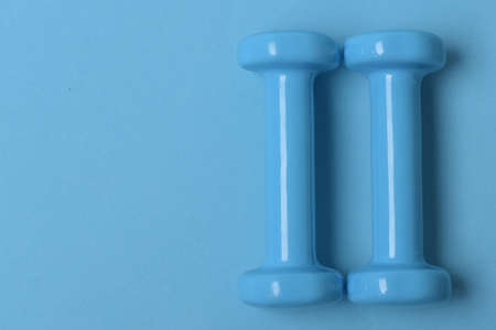 Barbells in small size, topview. Dumbbells made of blue plastic
