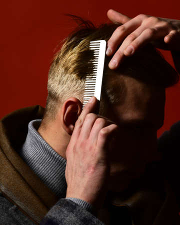 Stylist combing hair on red background. Man in vintage style