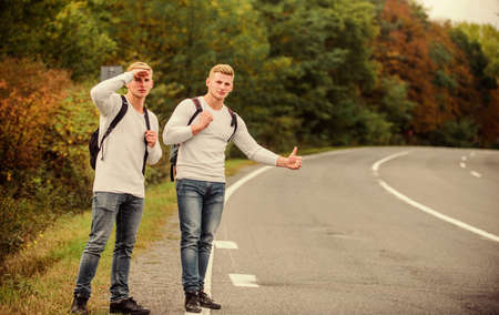 Travel and transport concept. Twins men at edge of road nature background. Reason people pick up hitchhikers. Missed their bus. Need help. Cheap transport. Transport problem. Try to stop some car