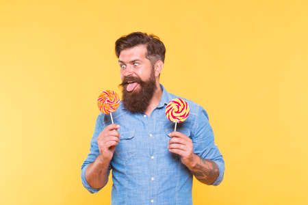 Crazy hungry hipster look at rainbow spiral colourful lollipop candy on sticks sticking out tongue yellow background, sweet tooth