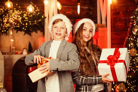 open gift. New Year 2020. Loving family with presents in room. brother and sister in santa hat. children happy time. Merry Christmas and Happy Holidays. exchanging gifts at decorated christmas tree Stok Fotoğraf
