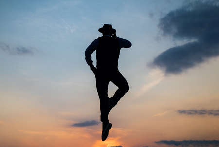 speaking on phone. man silhouette jump on sky background. confident businessman jumping. daily motivation. enjoying life and nature. business connection. freedom. Gear up to work mor
