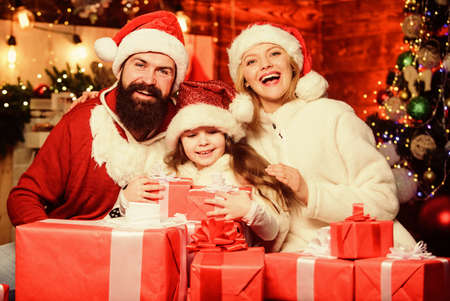 Happy New Year. Winter holidays. Shopping sales. merry christmas. Father and mother love daughter. small child and parents in santa hat. xmas gift boxes. Open present. Happy family celebrate new year
