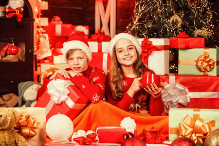 small kids relax under duvet white drinking milk. santa helpers among red present boxes. too much gifts. after successful shopping. childhood happiness and carefree. cosy winter evening together