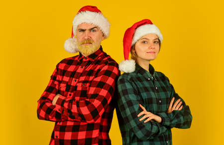 We love christmas. Couple in love enjoy christmas holiday celebration. Family wear santa hats. Entertainment ideas for adults. Santa team. Loving couple yellow background. Christmas magical time