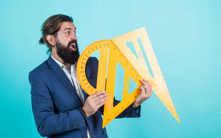 back to school. measure and size. surprised mature teacher holding triangle and protractor tool. bearded man engineer work with ruler. prepare for geometry exam. architecht or lecturer on math lesson Stockfoto
