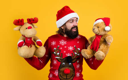 I wish. merry christmas. bearded man in santa claus costume. hipster celebrate xmas party with reindeer and bear toy. winter holiday preparations. present and gift shopping sale. happy new year
