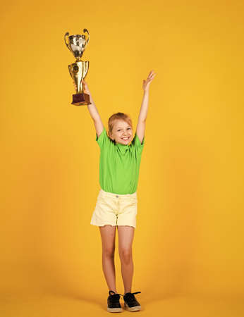 Great progress. Victory and win. Deserved award. Sport achievement. sport success concept. happy childrens day. happy childhood. small girl hold golden reward of championship cup. she is champion