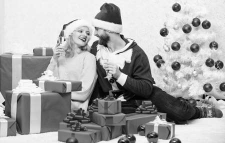 Celebrating christmas together. Couple in love enjoy christmas holiday celebration. Family tradition. Loving couple cuddle and drink champagne near christmas tree. Happy new year and merry christmas