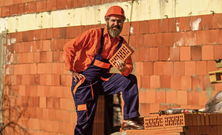 happy bearded man hold brick. brickwork. Man takes brick from the pile. Male construction worker holding brick. Repairman guy hard build up new layer level. build your own future. perfect quality