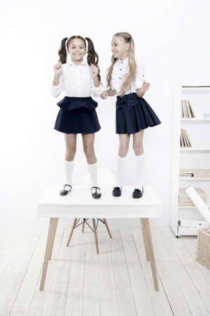 Back to school style. Happy small girls with long hair styles standing on desk in class. Little children smiling in school style. Giving school fashion a sense of style Imagens