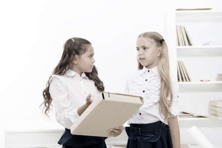 Needing homework help. Adorable small children holding file with homework in classroom. Doing homework assignment. Too much homework is bad for kids.