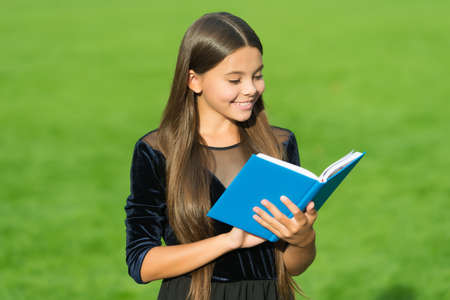 Feed the mind. Happy child read library book. Cute bookworm study green grass. School library. Reading and literacy education. Bibliotheca. Literature lesson. Satisfy the thirst of knowledge