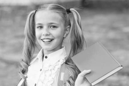 Book is uniquely portable magic. Happy schoolgirl hold book outdoors. Little reader. School library. Literature study. Reading habit. Book shop. Education and knowledge. Book you cant resist Reklamní fotografie