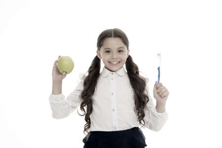 Dieting and health. Development of children. Little child smiling with tooth brush and green apple. Happy girl isolated on white. Teeth care and whitening. Good habit. Vitamin food for healthy teeth