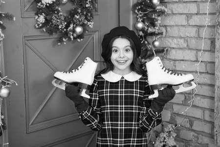 Winter is calling. Happy skater. Small child hold figure skates. Little girl enjoy winter activities. Winter sport. Figure skating. Happy winter holidays