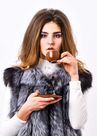 Woman splendid makeup wearing luxurious fur coat drinking hot coffee. Elite coffee concept. Enjoy luxurious aroma and taste hot coffee. Pretty lady drink coffee little ceramic cup white background