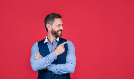 Look at this. Happy man point index finger red background. Objective pointing. Hand gesture. Marketing product or service. Indicating event or location. Pointing for direction, copy space