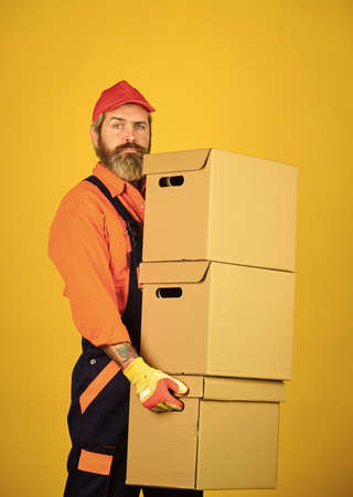 Man wearing boilersuit packing boxes. move to new apartment. bearded loader in uniform. Cardboard boxes - moving to a new house. purchase of new habitation or repair of room