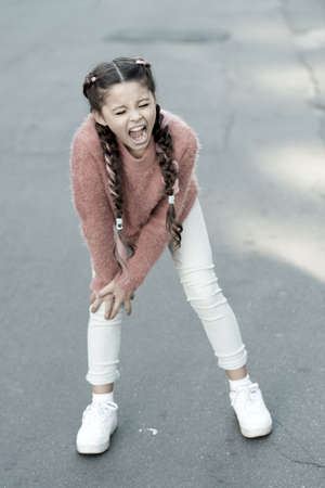 Small child has pain in knee. shouting little girl in autumn sweater. Autumn snuggles. Autumn fashion for pretty girl. healthy childhood. leg injury of little girl. Pure feelings. Melancholic mood