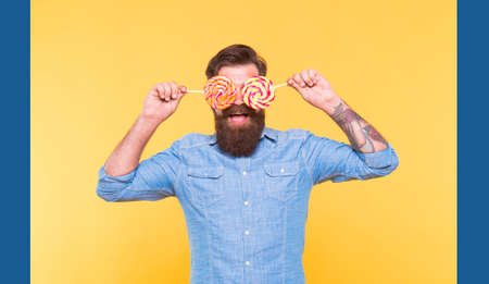 Funny bearded man hold sugar glasses rainbow swirl candy lollipops for birthday party holiday celebration yellow background, fun