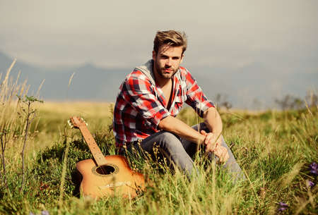 Let the Music Speak. hipster fashion. western camping and hiking. happy and free. cowboy man with acoustic guitar player. country music song. man with guitar in checkered shirt Stock Photo