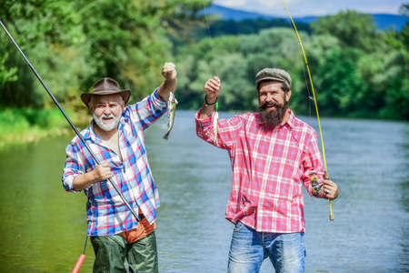 Mature man with friend fishing. Summer vacation. Happy cheerful people. Fishing freshwater lake pond river. Bearded men catching fish. Family time. Fisherman with fishing rod. Activity and hobby