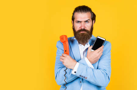 Choose your World. Then and Now. mature bearded man talk on retro phone. male hold smartphone. compare technology. mobile phone vs retro phone. business call. concept of technology progress Stock Photo