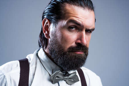 bearded caucasian man with moustache wear suspenders and bow tie, male retro fashion