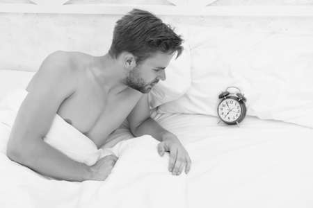 Sleepyhead. Sexy man check time in bed. Unshaven man lying in bed. Handsome man awake in morning. Sleepy person. Set alarm clock. Wake up early Foto de archivo
