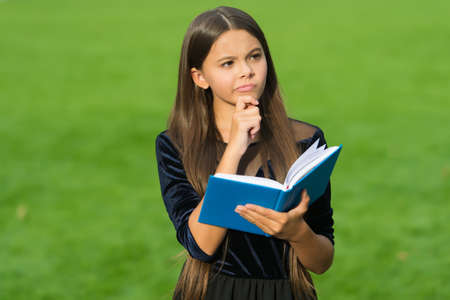Think clearly and rationally. Serious child think holding book green grass. Critical and creative thinking skills. Making decision. Doing homework assignment. Intellectual growth. Education school