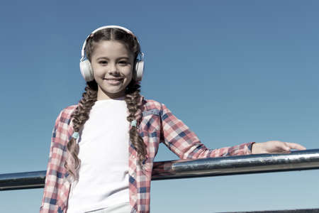 Kids headphones tested and ranked best to worst. Enjoy sound. Make your kid happy with best rated kids headphones available right now. Girl child listen music outdoors with modern headphones Banque d'images