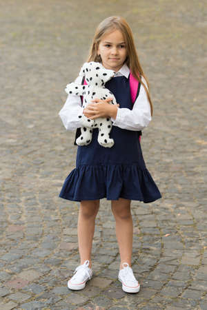 Caring is more gaining. Little child in school uniform hold toy dog outdoors. Pet animal. Friends and friendship. Child care and childhood. Learn and play. Preschool education. Childrens day