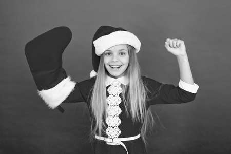 Power of xmas. Little Santa flex arms. Happy child show strength. Small girl celebrate xmas and new year. X-mas eve. Merry xmas. New Year. Christmas party. Festive season. Xmas comes but once a year 版權商用圖片