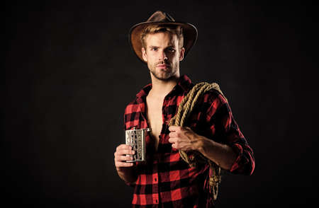 Always drink upstream from the herd. Vintage style man. Wild West retro cowboy. cowboy with lasso rope. Western. wild west rodeo. man in hat black background. man checkered shirt on ranch Stockfoto