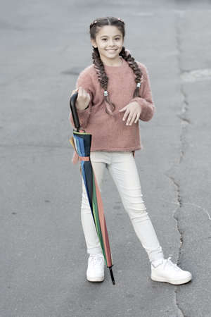 Girl child long hair ready meet fall weather with folded umbrella. Carefree weekend walk. Fall season. Colorful fall accessory positive influence. Brighten your fall mood. Ready for any weather