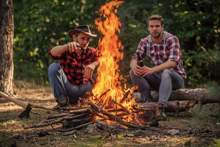 Pathways Into Nature. hike and people. two men relax at fire. hiking and camping. male friendship. man drink beer at bonfire. ranger at outdoor activities. picnic weekend in nature. Adventure concept Reklamní fotografie