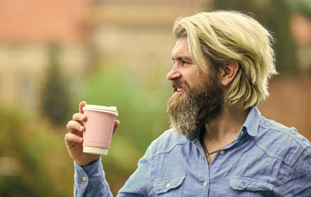 Tasty breakfast. bearded man drinking coffee while walking outdoors. bearded hipster guy wearing casual clothes enjoys relaxing on weekend. morning drinks concept. student on coffee break