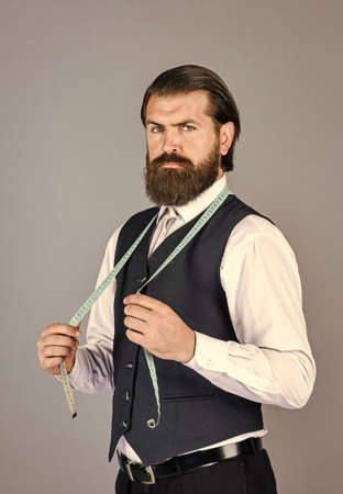 handsome tailor in white shirt working. amazing atelier with antique furniture. portrait of tailor-made custom-made suit for model. Business shirt tailoring in store with measuring tape