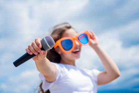 make your voice louder. Music and life. teen girl singing song with microphone. having a party. Happy kid with microphone. Singing Songs in karaoke. Lifestyle and People Concept. selective focus Foto de archivo