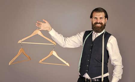 best design. portrait of man holding hanger. tailor man use tape measure. professional male sartor with measuring tape and hanger. Handsome man in smart casual wear is holding hanger Standard-Bild