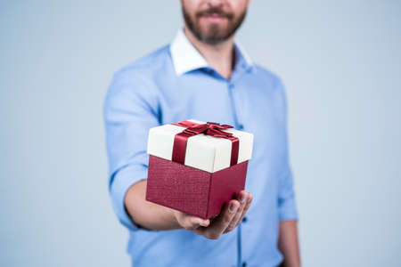Man cropped view gift present box pack tied with red ribbon selective focus, gifting Stock Photo