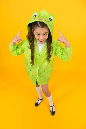Rainproof accessories make rainy fall day pleasant. Waterproof accessory. Kid girl happy wear raincoat. Cute raincoat kids would love. Frog style. Schoolgirl hooded raincoat enjoy fall weather Imagens