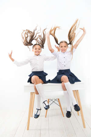 Healthier hair from root to tip. Adorable little girls with flying hair sitting on desk. Cute small children with long hair ponytails wearing school uniform. Luxurious hair extensions