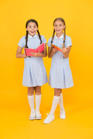 Sincere interest. Little girls with encyclopedia or childrens books. School library. Educational books for school. Reading books. Reading and retelling. Small children holding books yellow background 免版税图像