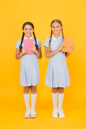 Educational books for schools. Reading books. School library. Homeschooling concept. Literacy club. Cute children holding books on yellow background. Little girls with encyclopedia or childrens books
