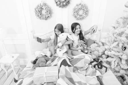 Enjoying selfie shooting. Happy little children with mobile phone. Little girls use phone in bed. Making Christmas and New Year selfie with smartphone. Merry Christmas and Happy New Year greetings
