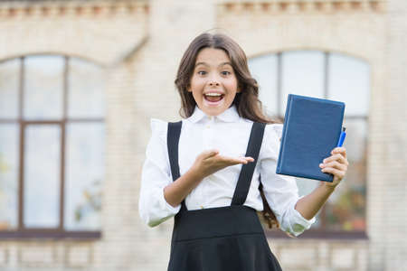 Best textbooks for learning at home. School education concept. Knowledge day. Learning language. Hooked on learning. Cute smiling child hold book. Pass test successfully. Little girl school student