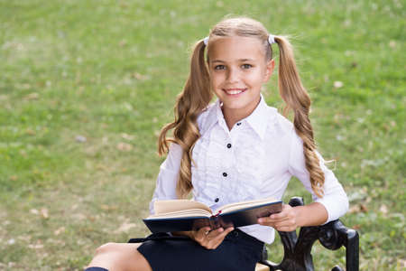 Study language. Cute smiling small child hold book. Adorable little girl school student. School education concept. Cute little bookworm. Knowledge day. Ready for lessons. Secondary school student