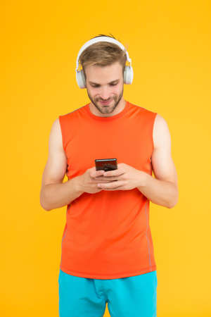 cheerful bearded man listen music in digital earphones using mobile phone app wearing sporty clothes for workout, social network